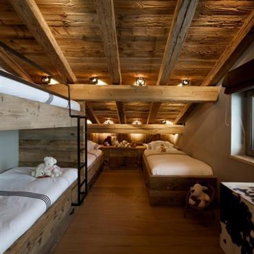 Dortoir pour enfants avec lits montagne superposés en vieux bois et poutres apparentes