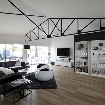 Le salon lumineux, en noir et blanc, réchauffé par le carrelage imitation parquet ouvrant sur la terrasse.