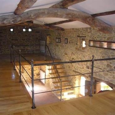 Mezzanine et escalier en bois jaune. Murs en pierres apparentes, poutres apparentes.