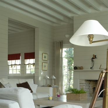Salon avec poutres apparentes blanches, cheminée