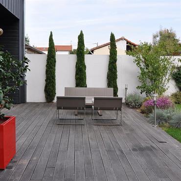 Terrasse en bois dans un jardin de ville avec équipements design