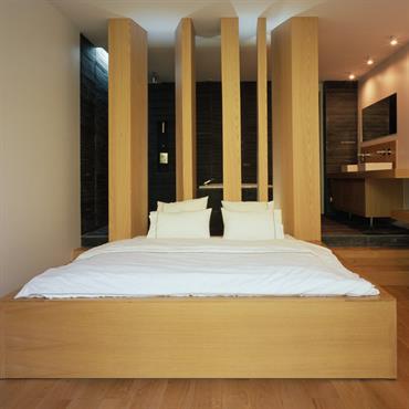 Claustras en tête de lit séparant la chambre de la salle de bain. Le bois réchauffe l'espace nuit