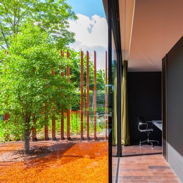 Les lames en acier Corten agissent comme une protection, apportant de l'intimité à la maison et la protégeant du soleil