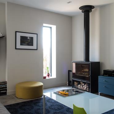 Salon moderne avec poêle à bois et touches de couleur