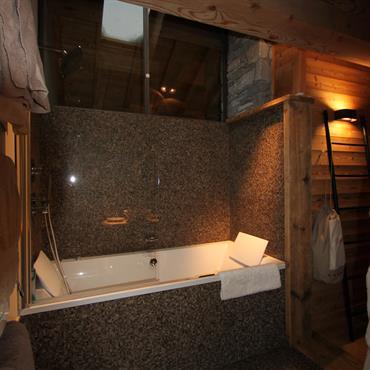 Ambiance intime et tamisée dans la salle de bain. Baignoire 2 places, mosaïque grise
