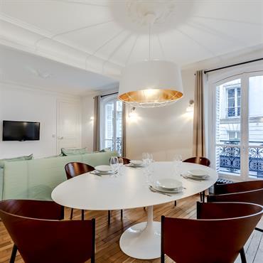 La table design ovale que surplomble une suspension imposante crée, avec les fauteuils en bois, un coin repas confortable et convivial.