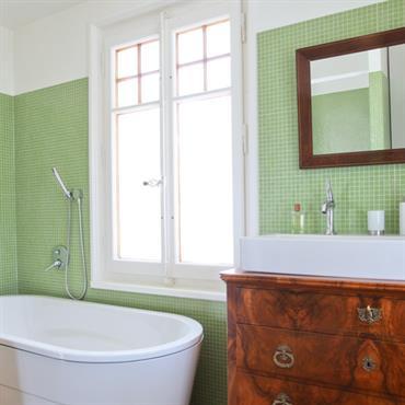 Salle de bain avec carrelage en mosaïque verte. Commode ancienne sous le lavabo