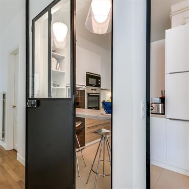 Verrière en acier repliable sur elle-même, qui permet de disposer d'une cuisine ouverte ou fermée selon les besoins.
