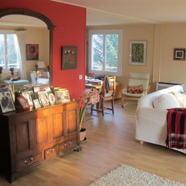 Salon avec un mur ocre. Canapé blanc et meubles anciens