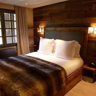 Chambre façon montagne. Parquet en bois clair. Mur de tête de lit en bois plus foncé