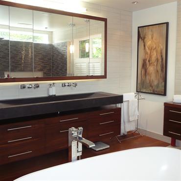 Salle de bain avec plan vasque et meuble sous vasque suspendu en bois.