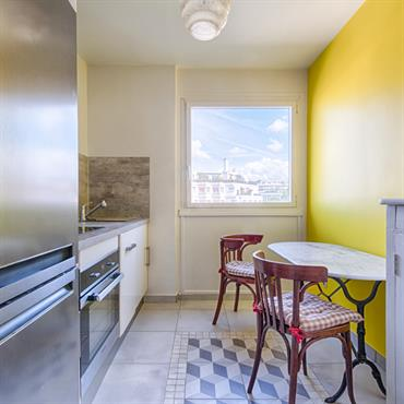 Le mur jaune apporte de la luminosité à cette cuisine d'appartement