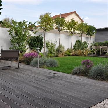 Jardin de ville avec terrasses en bois, gazon et plantations d'ornement.