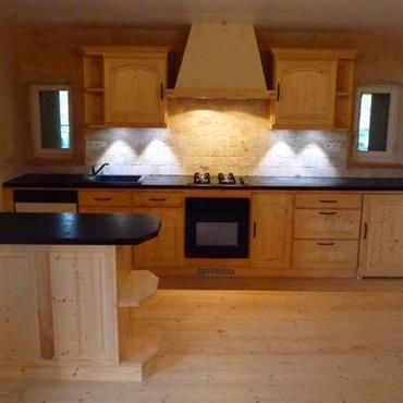 Harmonie de bois clair dans cette petite cuisine qui mise sur les matériaux naturels avec sa crédence en pierre.