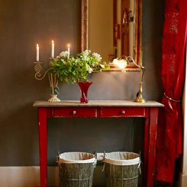Console rouge avec paniers pour l'organisation et esthétique d'une entrée.