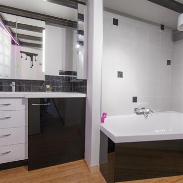 Salle de bains moderne noir et blanc, plan vasque et meuble sur mesures, paroi en pavés de verre.
