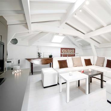 Salon lumineux sous les combles. Murs, sol, plafond et poutres apparentes en blanc. Touches de marrons et gris dans les accessoires