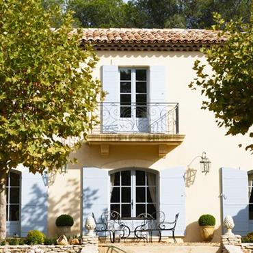 Façade provençale traditionnelle avec enduit clair, volets en bois et balcon au garde corps en fer ouvragé.
