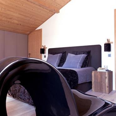 Une chambre au confort feutré, toujours dans les tons de bleu marine pour une cohérence de tons et d'ambiance dans l'ensemble de ce chalet contemporain.