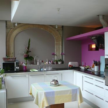 Cuisine moderne blanche et grise, plan de travail noir. Touches de rose et de vert