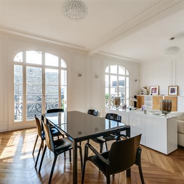 La salle à manger jouxte le salon dans cette grande pièce ouverte. Les deux espaces sont séparés par un meuble bas laqué blanc.