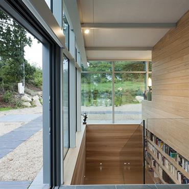 Cage d'escalier vitrée et bibliothèque