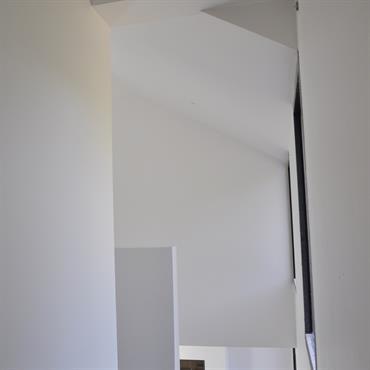 Perméabilité du regard, mise en perspective des espaces. Depuis le couloir des chambres enfant, une vision dérobée du séjour.