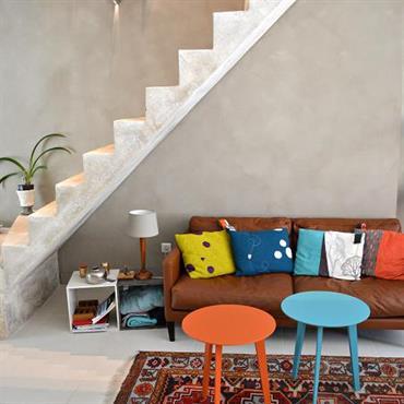 L'escalier suspendu en béton se détache contre le mur à la chaux. Tables de salon réédition de mobilier des années 70.