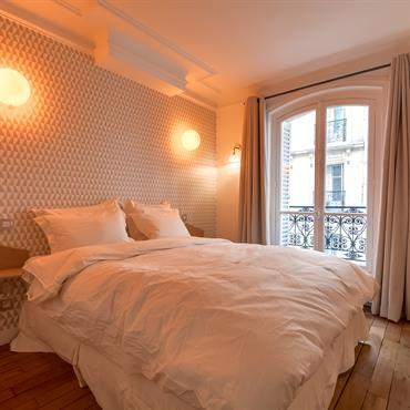 Tonalités neutres, literie douillette et domainante de bois créent une atmosphère chaleureuse dans la chambre.