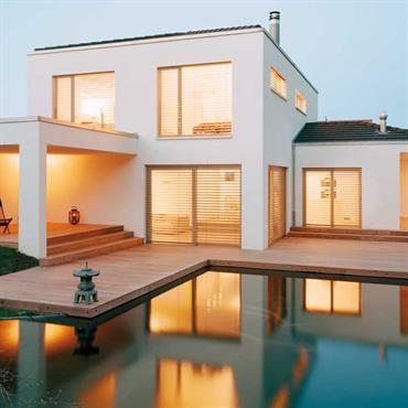 Maison blanche contemporaine ouverte sur le jardin. Terrasse en bois, piscine et pelouse