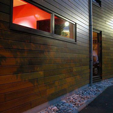 Le bois du bardage extérieur a été vernis dans une teinte oranger proche des briques des maisons du quartier.