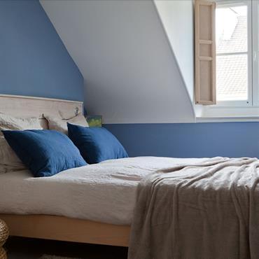 Chambre bleue mansardée de style scandinave avec lit en bois