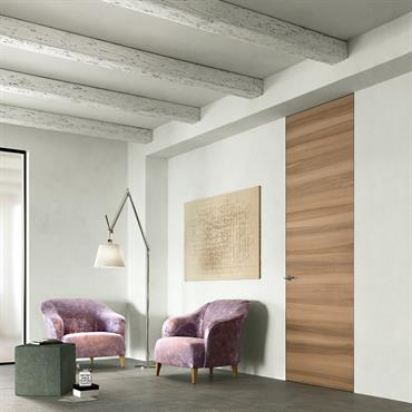 Petit salon avec porte en bois et poutres apparentes