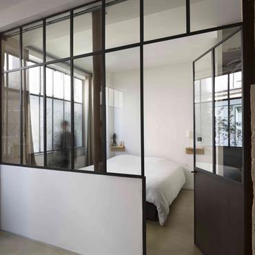 Pour la connecter à la lumière, la chambre parentale se vit derrière une structure en verrière atelier. Elle dispose de sa propre salle de bains et se glisse dans l'intimité ...