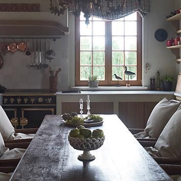 Cuisine avec chaises anciennes en rotin. Table ancienne en bois massif. Portes des meubles de cuisine façon bois ancien