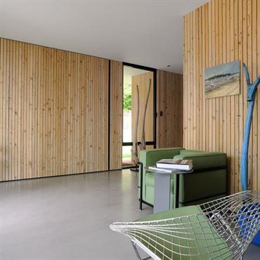 Derrière le panneau de bois se cache un caisson lit. Les cloisons offrent des portes coulissantes pour transformer cet espace de vie ouvert en vraie chambre d'amis confortable.