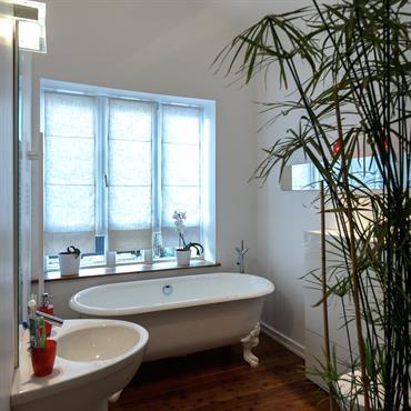 La baignoire occupe toute la largeur de la pièce et se place sous la fenêtre. Les papyrus anime la pièce et dissimulent le meuble toilettes. La sobriété du lavabo contemporain ...