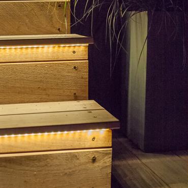 Escalier d'extérieur en bois, marches éclairées par des guirlandes de led