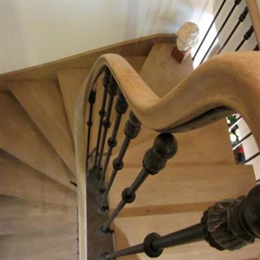 Escalier demi tournant en bois et fer forgé.