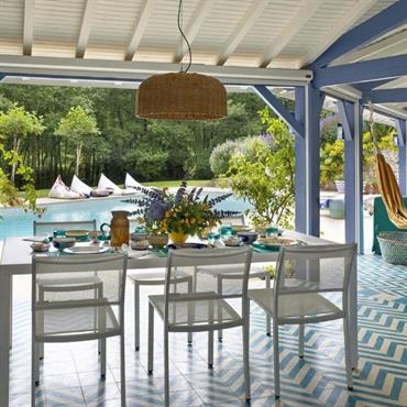 Terrasse abritée déco d'été en bleu et blanc avec salle à manger d'extérieur