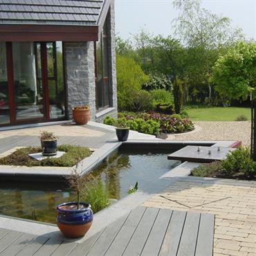 Jardin avec bassin. Allée en bois et pavés