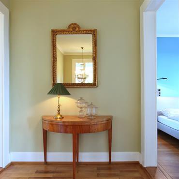 Couloir avec demie-table ronde ancienne. parquet