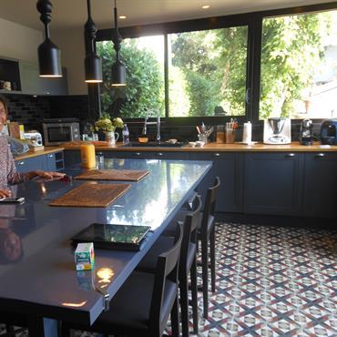 Cuisine au carrelage à losanges ancien, meubles gris foncé, plan de travail en bois jaune