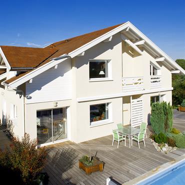 Maison avec terrasse bois et piscine. Façade blanche avec bais vitrées. Balustrade du balcon en bois blanc