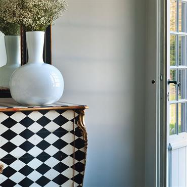Entrée avec meuble ancien à motifs géométriques en losanges noirs et blancs