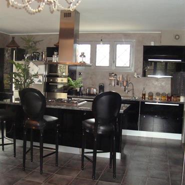 L'ensemble de l'espace a été traité avec un tadelakt gris, un carrelage grand format gris, du mobilier laqué noir et des accessoires dorés et argentés.