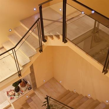 Escalier en bois sur un plan carré. Garde corps en verre, structure acier.