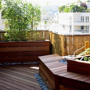 Terrasse de ville avec canisses brise vue, plancher de bois, jardinière en bois plantée de bambous et belle composition de plantes