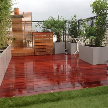 Terrasse en bois exotique (padouk) et gazon artificiel synthétique. Les bacs en aluminium peints, plantés d'une végétation haute permettent de masquer le vis à vis.