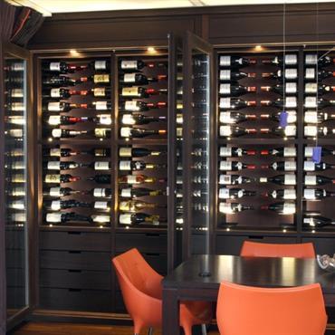 Salle à manger avec cave à vin design. Chaises en plastique orange clair